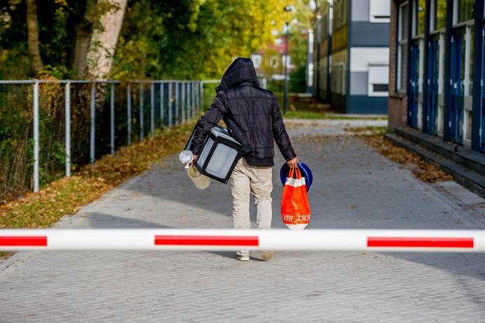 Een bewoner van een azc in Amsterdam loopt naar zijn verblijfplaats.