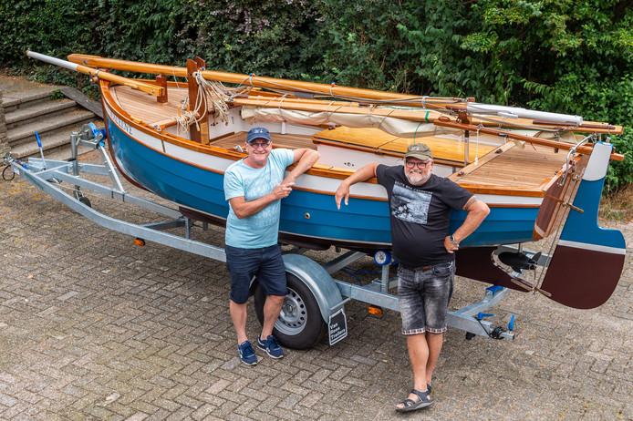 Frank Vergeer (links) en zijn broer John naast de door hen zelf gebouwde houten zeilboot waarmee zij in de prijzen zijn gevallen.