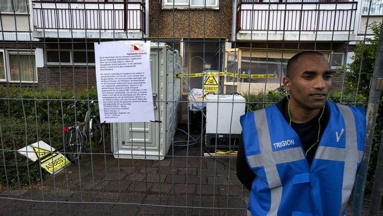 Een particulier beveiliger staat voor een met asbest verontreinigd portiek aan de Marco Pololaan. Beeld anp