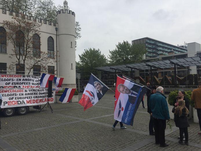 Pegidabetogers met vlaggen Marine Le Pen en Geert Wilders.