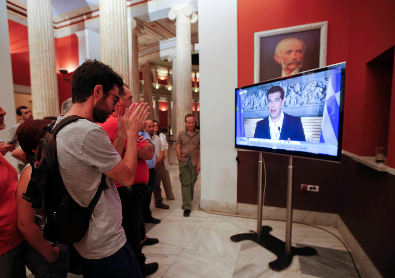 Grieken kijken naar de persconferentie van premier Tsipras.
