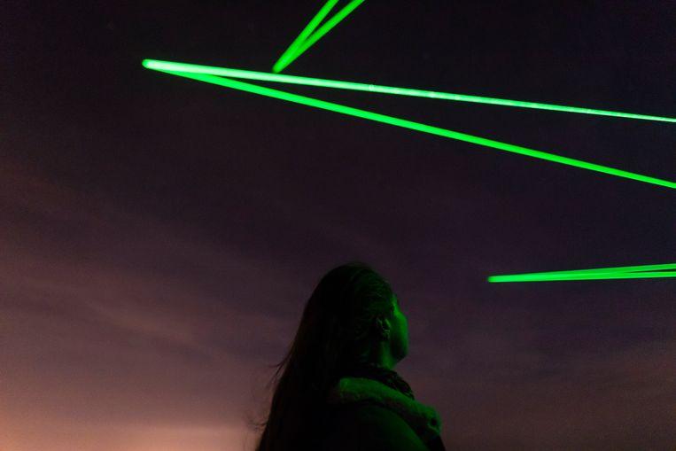 Wie vanavond naar het Nederlandse Almere afzakt, kan zien hoe laserstralen de stukjes afval volgen terwijl ze overvliegen.   Beeld Willem de Kam
