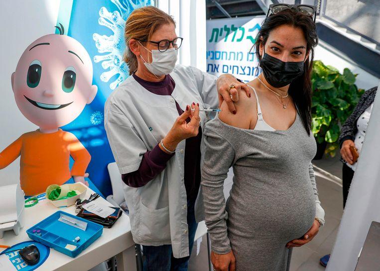 Een zwangere vrouw wordt gevaccineerd tegen het coronavirus in Tel Aviv, 23 januari 2021.  Beeld AFP
