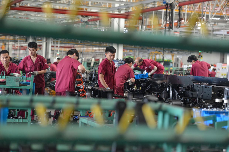 Medewerkers bij een lopende band in een fabriek in Fuyang, China. De Chinese economie herstelt zich onverwacht snel. Beeld AFP