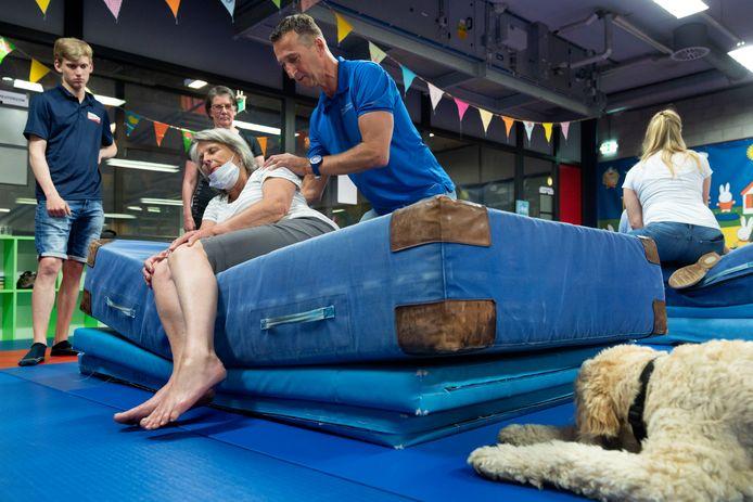Dorothee Dalmeijer met haar blindengeleidehond Kendra werkt samen met fysiotherapeut Leon Rijken aan het veilig leren vallen.