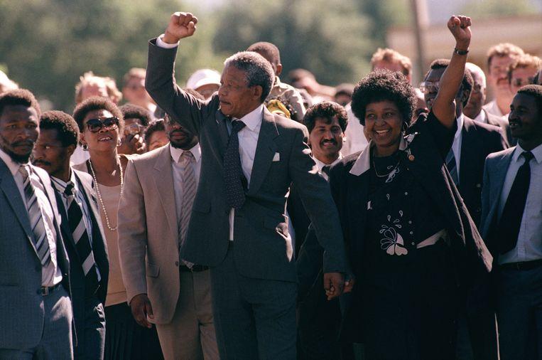 11 februari 1990: Nelson Mandela verlaat met zijn vrouw Winnie de gevangenis in Kaapstad, nadat hij 27 jaar opgesloten heeft gezeten.  Beeld AP