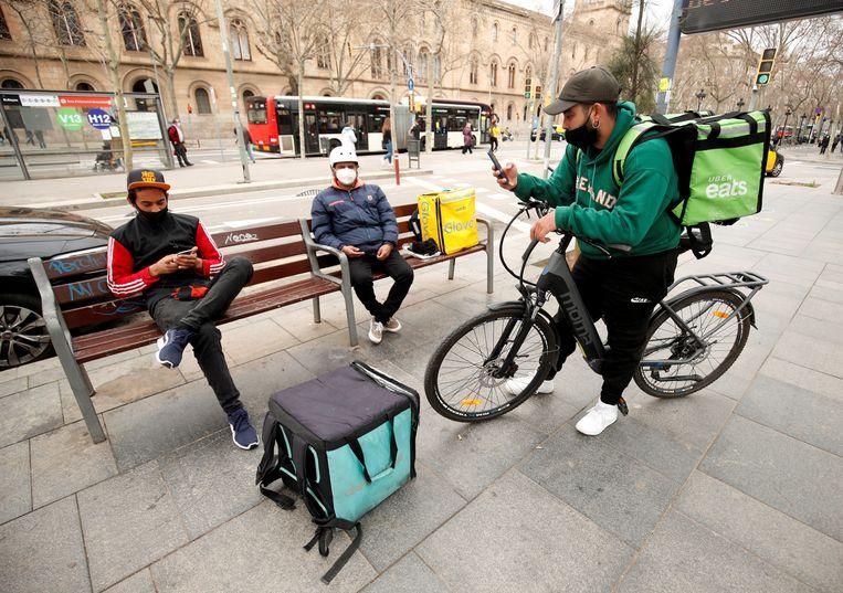 Maaltijdbezorgers van Glovo, UberEats en Deliveroo in Barcelona. Beeld REUTERS