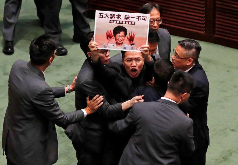 Een protesterend oppositielid wordt de zaal uitgezet.