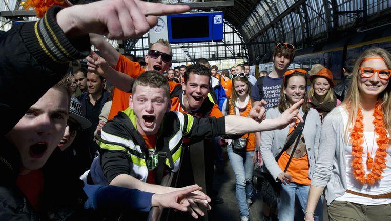Feestvierders op Amsterdam Centraal Station zijn er klaar voor om in de hoofdstad Koninginnedag te gaan vieren. Beeld ANP