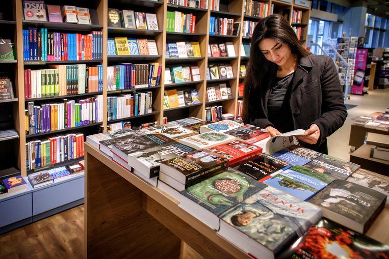 Bezoeker bladert door boeken van de StudyStore. Beeld Dolph Cantrijn / Hollandse Hoogte