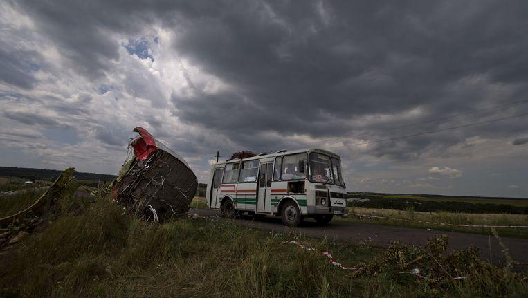 Een Oekraïense bus rijdt langs de plek waar vlucht MH17 van Malaysia Airlines neerstortte. Beeld ap