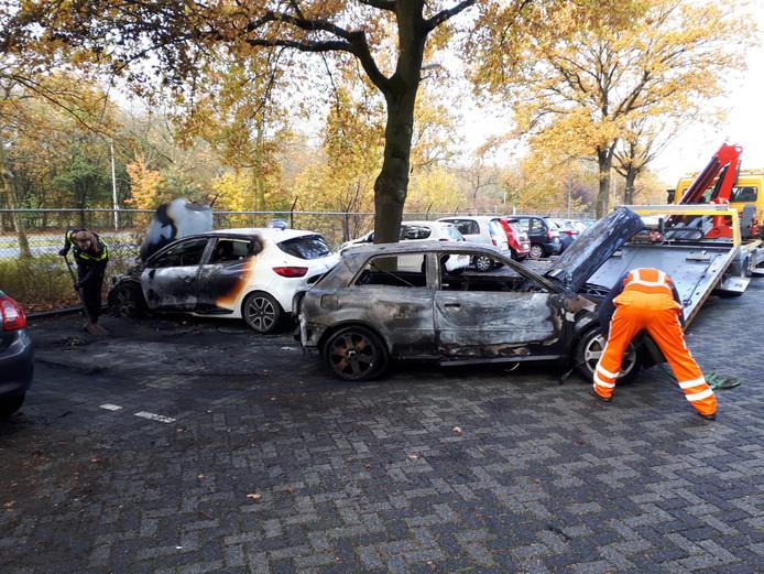 Een van de uitgebrande auto's wordt afgevoerd, terwijl een politieagente de parkeerplek schoonveegt.
