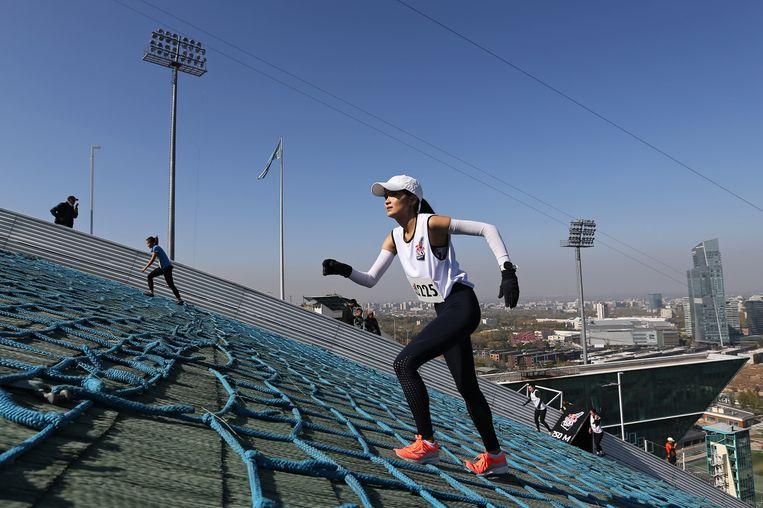Deelnemers aan de Red Bull 400 bewegen zich zo snel mogelijk omhoog op de internationale skischans in Almaty, Kazachstan. Bij deze moordend zware discipline, van de voet tot de top van een skischans, moeten stijgingspercentages tot wel 75 worden bedwongen. De touwen liggen er voor extra grip.  Beeld REUTERS