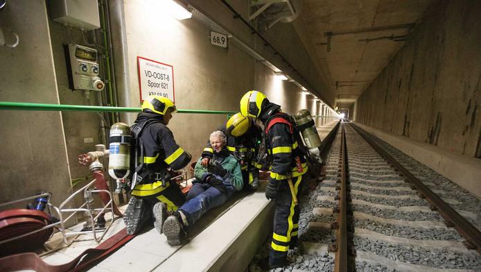 Hulpverleners helpen een man tijdens een calamiteitenoefening in de nieuwe spoortunnel in Delft.
