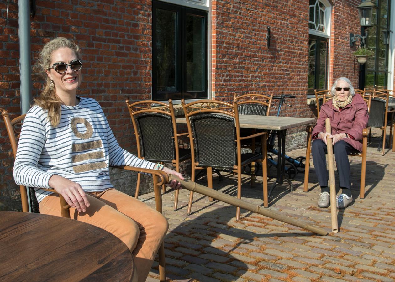 Kim Bakker met mevrouw Lantsheer, een van de bewoonsters van Landgoed Rijckholt. De stokken herinneren eraan om anderhalve meter afstand te bewaren.