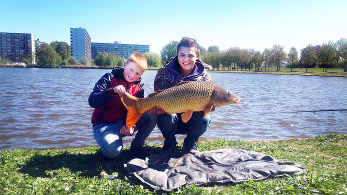 Nathan (rechts) en Djowie Tuitel zijn trots op hun zojuist gevangen karper van 12 kilo in de Ringvaartplas in de Rotterdamse wijk Prinsenland. Vissen is populair tijdens de coronacrisis.