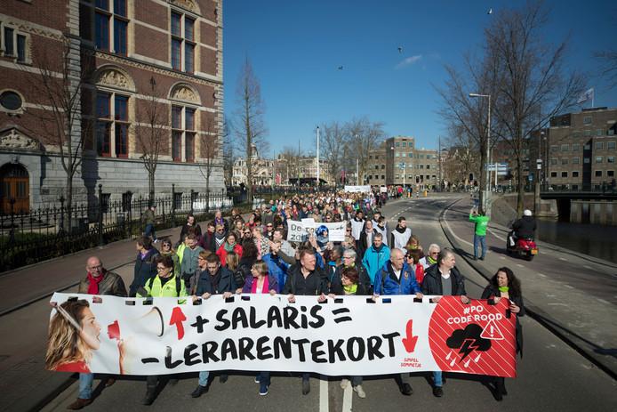 Leraren dragen een spandoek met zich mee tijdens een demonstratieve mars in maart in Amsterdam van zo'n 20.000 leerkrachten tegen de lage salarissen en te hoge werkdruk.