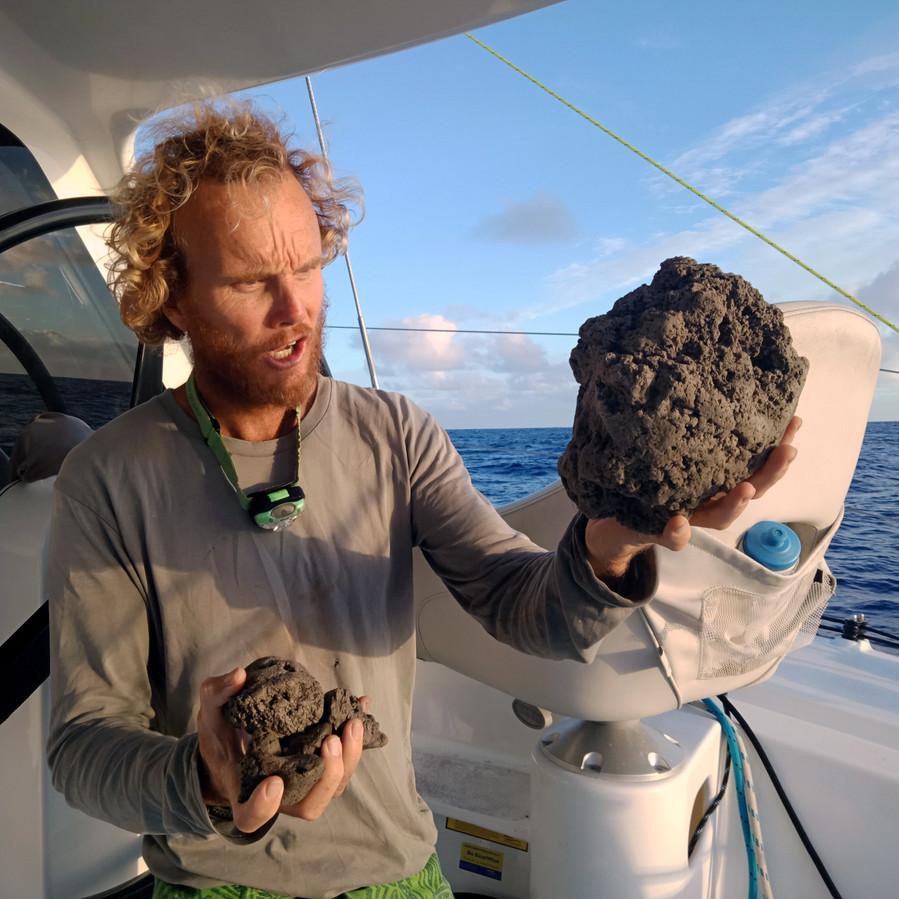 Michael Hoult houdt puimstenen in zijn handen op zijn boot nabij Tonga.
