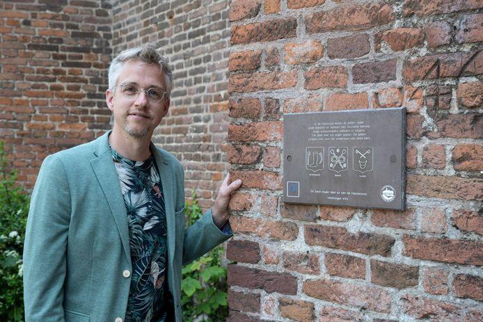 Hendrik Haafkens van het Erfgoedcentrum Zutphen voor een van de verouderde monumentenbordjes bij de Walburgiskerk.