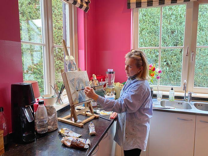 Brigitte legt in haar keuken de laatste hand aan het portret van Rex.