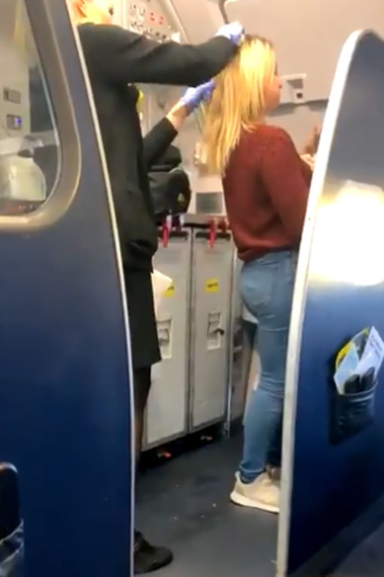 Het haar van de vrouw wordt door een stewardess gereinigd.