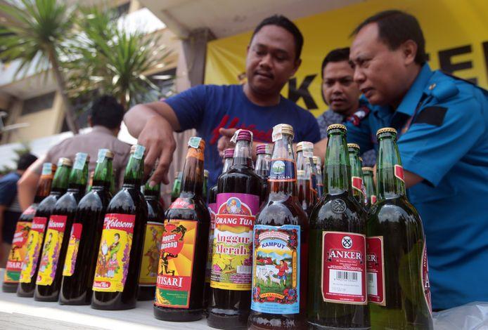 Indonesische agenten laten zelfgebrouwen alcohol zien tijdens een persconferentie op 11 april 2018.