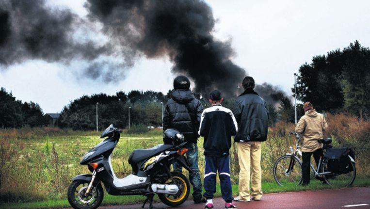 Omstanders kijken naar de zwarte rookpluimn van de brand. Foto Floris Lok Beeld