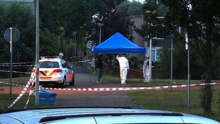 De politie onderzoekt het plaats delict op de Antwerpenbaan, waar Inchomar B. in 2013 werd neergeschoten. Beeld Politie.nl