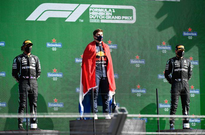 Max Verstappen wordt op het podium geflankeerd door Lewis Hamilton (l) en Valtteri Bottas.