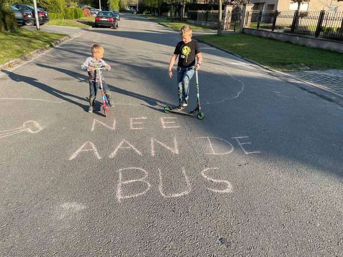 """De boodschap is duidelijk: """"Nee, aan de bus!"""" Kinderen schreven afgelopen weekend boodschappen op het wegdek in de Wachtebekestraat."""