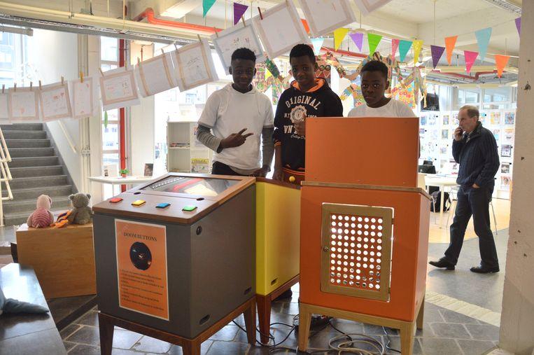 Aristophane (15), Elihu (14) en Jayden (13) testen de Arcade Games of speelkasten uit in de bib van Ninove.