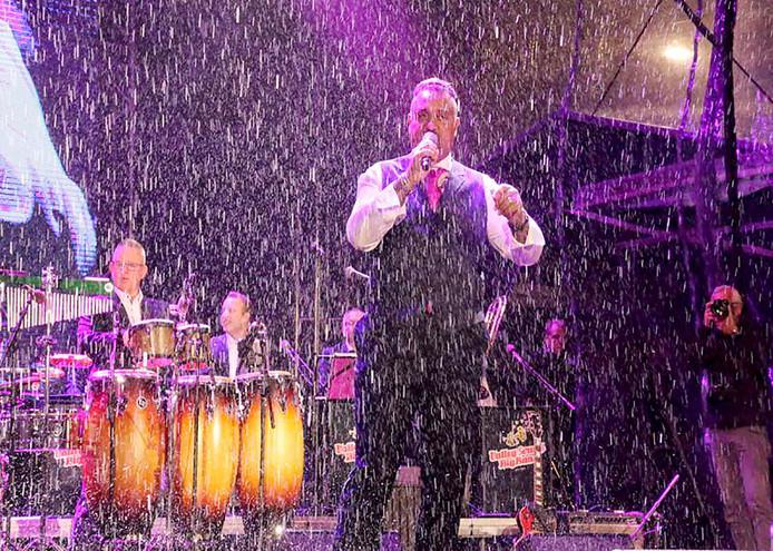 Haroun zingt in de regen met Valley Sound Big Band tijdens opening feestweek voor Roosendaal 750 jaar op de Markt. Foto Leo de Jaeger
