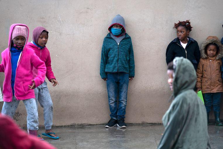Kinderen schuilen voor de regen in Zuid-Afrika. Beeld EPA