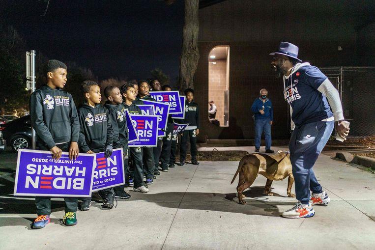 Kinderen met Biden-bordjes voor een stembureau  in Minneapolis, Minnesota. Beeld AFP