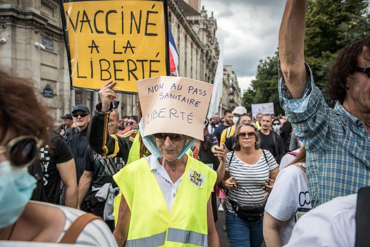 In Parijs draagt een vrouw een protesthoed: 'Nee tegen de gezondheidspas'. Voor het eerst sinds het begin van de coronacrisis gaan Fransen massaal de straat op Beeld EPA
