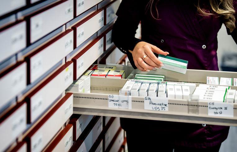 Een apothekersassistente zoekt medicijnen bij elkaar in een apotheek. Als farmaceuten te veel vragen, adviseert het Zorginstituut dat de minister gaat onderhandelen. Beeld ANP