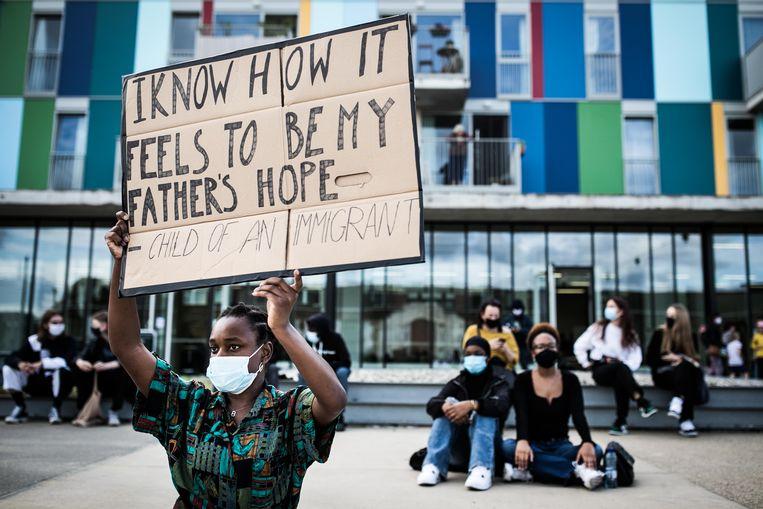 Een zwarte vrouw houdt een bord vast met daarop: 'Ik weet hoe het is om mijn vaders hoop te zijn.' Met daaronder: 'Kind van een immigrant.' Beeld Bas Bogaerts