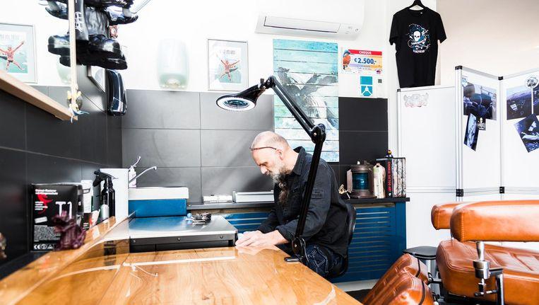 In een betegelde hoek staat een grote, bruine kunstleren stoel voor klanten. Aan de muren hangen gesigneerde foto's en actiefiguren Beeld Tammy van Nerum