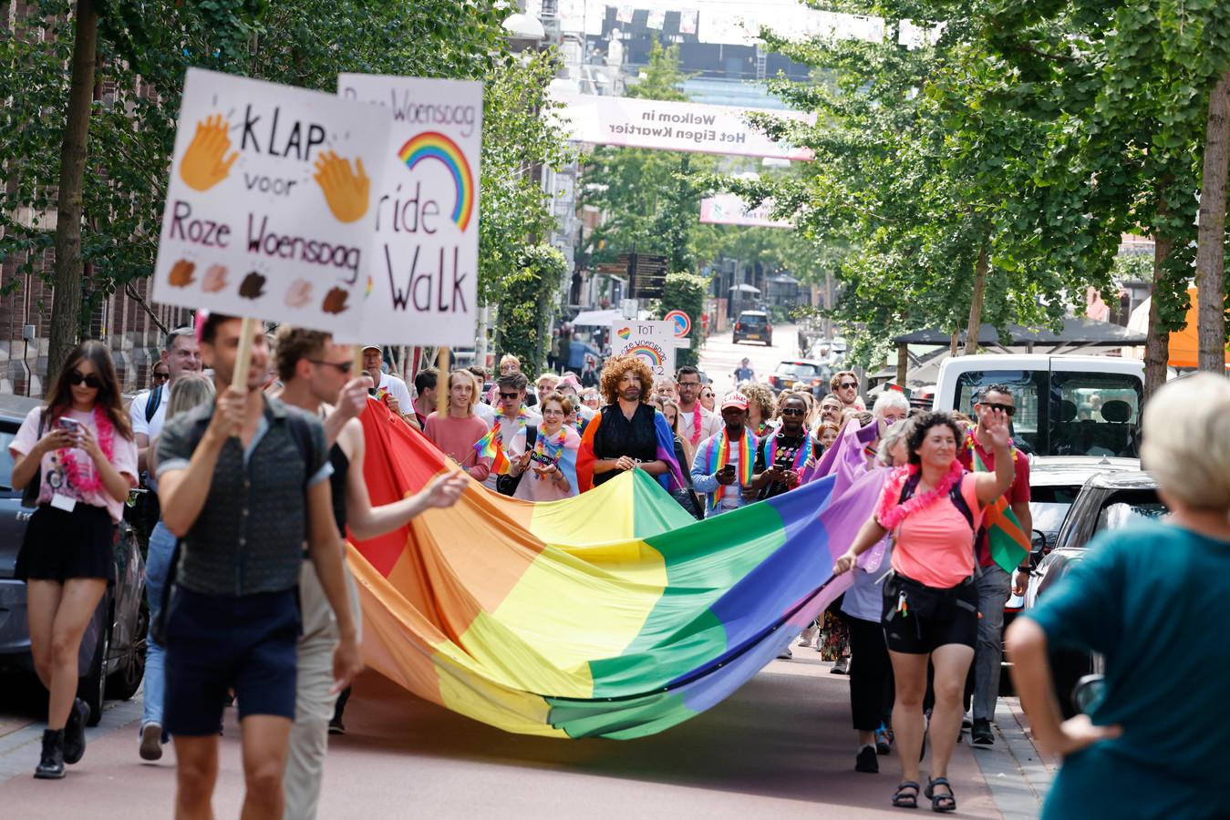 De regenboogvlag wordt door de stad gedragen.