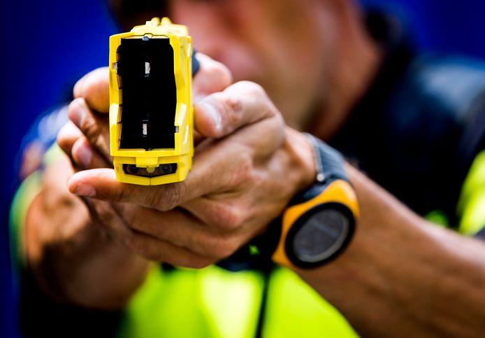 Een politieman hanteert het stroomstootwapen, ook wel taser genoemd.