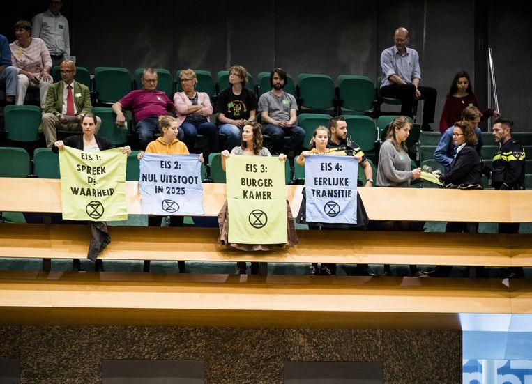 Leden van de actiegroep Extinction Rebellion verstoren de stemmingen tijdens het vragenuur in de Tweede Kamer.  Beeld ANP - Bart Maat