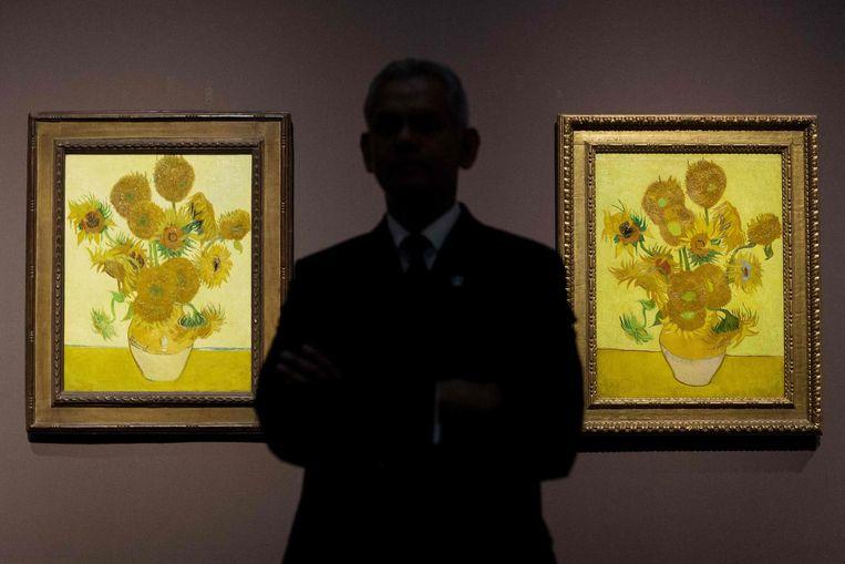 Een beveiliger voor de twee Zonnebloemen in de National Gallery. Beeld AFP