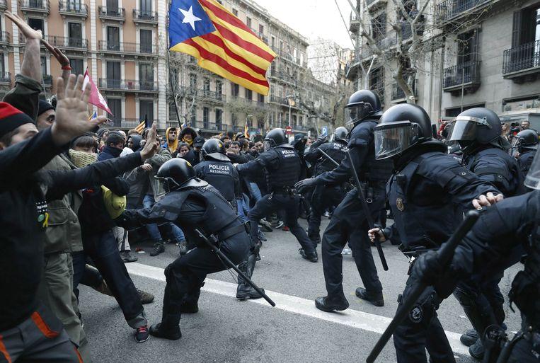 De oproerpolitie slaat betogers terug bij de zetel van de Spaanse regering in Barcelona. Beeld EPA