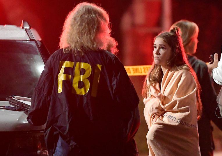 Een FBI-agent praat met een bezoeker van de Borderline-bar in Thousand Oaks. Beeld AP