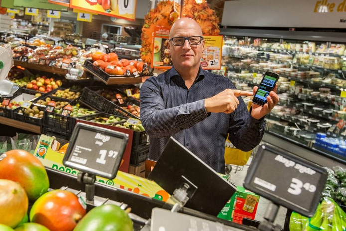Hans Kok van Jumbo Kok toont de nieuw app in zijn supermarkt.