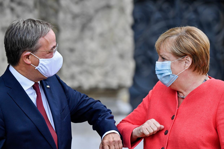CDU-voorzitter Armin Laschet en zijn partijgenote Angela Merkel begroeten elkaar op coronaveilige wijze. Het is aan Laschet om  de crisis in zijn partij te bezweren, met het oog op de Bondsdagverkiezingen over een halfjaar. Beeld AP