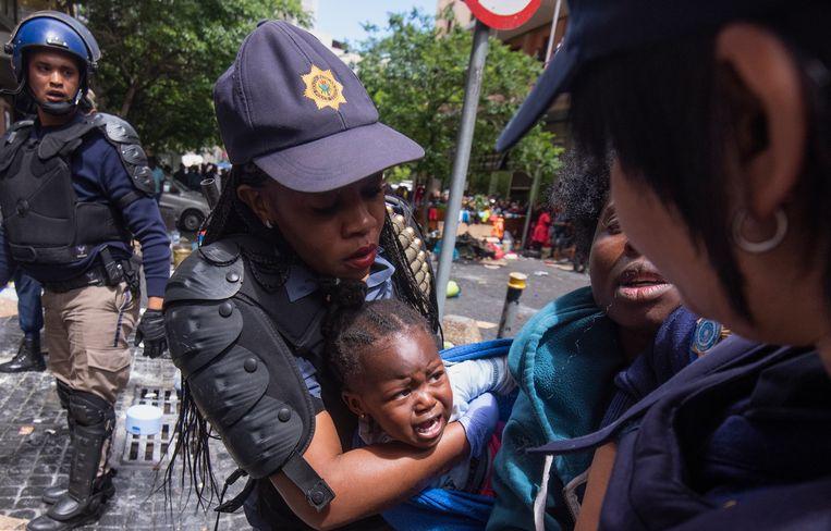 Voor het kantoor van VN-organisatie UNHCR wordt een baby door de politie van haar moeder gescheiden. Beeld EPA