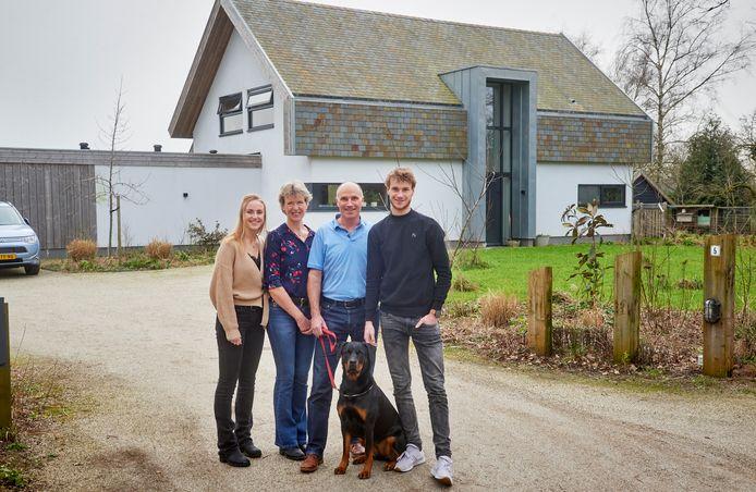 De familie Langens bij hun energiezuinig huis in Heesch dat van duurzaam milieuvriendelijk materiaal is gemaakt. Vlnr: Eva, Marian, Jan-Paul en Olaf, samen met rottweiler Roef. Achter het huis is een voedselbos, maar ook in de voortuin is er wat te 'eten'.