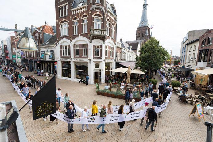 Tilburg valt even stil als het lint met 160 namen door de binnenstad wordt gedragen.