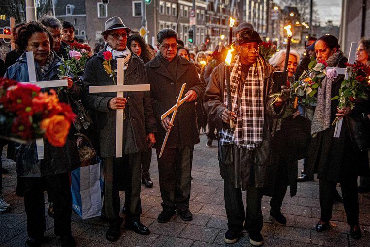 Deelnemers  bij de herdenking van de Decembermoorden vorig jaar in Amsterdam. Beeld ANP